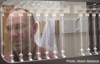 Scientist's face reflecting on the front of a DNA sequencing machine.