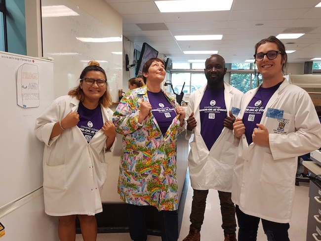 Photo of the four fabulous teachers of Hands-on at Otago Biochemistry showing off their Hands-on T-shirts under their lab coats.