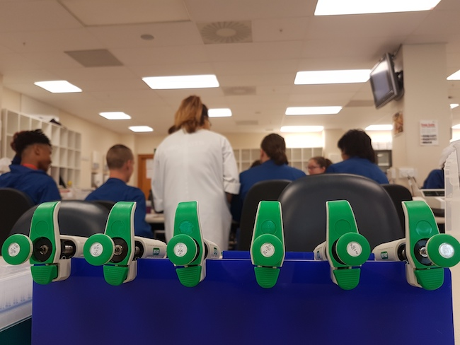 Photo of a line of six green-handled pipettes with a lab class in the background.