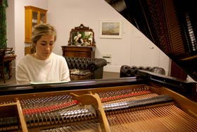 A student playing Carrington's grand piano