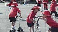Photo of several primary school children with sun hats on, riding scooters around their school yard.