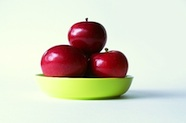 Photo of 3 red apples in a green bowl