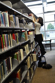 Photo of a young woman standing on a step stool arranging books on a high bookshelf