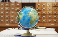 Photo in a library of a world globe on a desk in front of a wall of wooden catalogue filing drawers