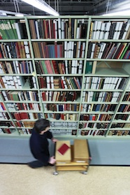 Photo of library shelving with staff member pushing trolley in foreground