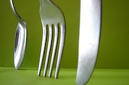 Photo of spoon, fork and knife standing against a green background