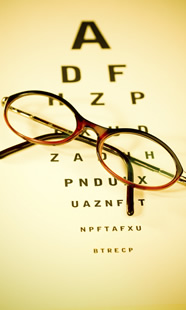 A pair of glasses resting on an eye chart