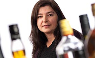 Professor Jennie Connor standing behind alcohol bottles