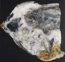 Quartz vein material containing lumps of schist, forming a breccia (cemented fragmental rock). The specimen is 20 cm across. Shiny iron minerals (pyrite, arsenopyrite) less than half a centimetre across are visible scattered through the breccia. These contain the gold. Gold is rarely found as larger pieces in the quartz.