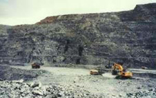 Macraes open-pit hard-rock gold mine near Dunedin. The mine extends deep into the unoxidised schist, following a gold-bearing zone which slopes gently northeastwards. Each bench is 10 metres high. The thin zone of oxidised schist can be seen at the top of the pit