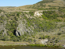 Broken formation (sheared greywacke; left) at Fiddlers Flat in the Manuherikia River gorge. White rocks in upper centre are Miocene sediments of the historical alluvial gold mine, and clay-altered greywacke immediately beneath the sediments. The boundary between sediments and basement (unconformity) dips gently to the right, and this zone contained the most abundant alluvial gold.