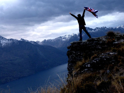 Robin Andrews doing a king of the world pose with nz-flag in arm and NZ remarkables in the background