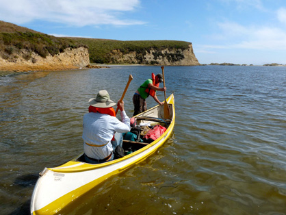 Robert W. Boessenecker and Richard Hilton departing in a canoe. Sandsotne cliffs in the background