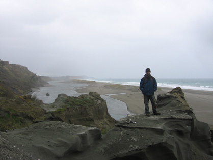 Robert Boessenecker stands on a mudstone spur by the beach. It is a gloomy overcast day