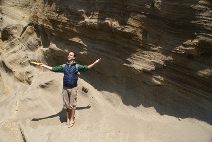 Ben Moorhouse posing in front of a bedded outcrop with arms outstretched