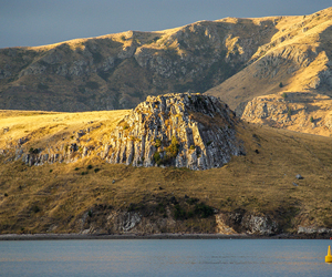 Basalt outcrops at Purau Bay, Banks Peninsula forming part of the 5.8-8.1Ma Diamond Harbour Volcanic Group. The Port Hills in the background are composed of an older 9.7-11Ma sequence.