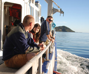 Fair winds and a following sea: Andrew Gorman, Jess Hinojosa, Bob Dagg, and Claudine Sterling soak up some Fiordland sun as Otago's R/V Polaris II rounds Puysegur Point at the end of a successful field season.