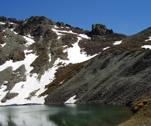 An alpine tarn surrounded by snow capped schist.