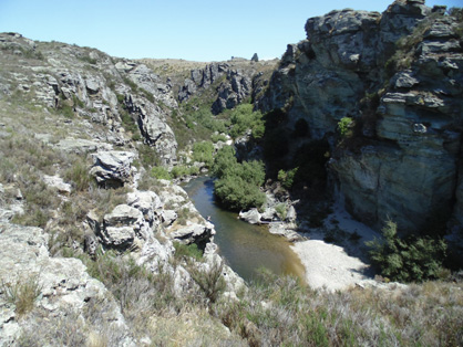 Manuherikia River gorge downstream of the historic Daniel O'Connell Bridge, Ophir. The river is cutting down into schist bedrock, as the gentle northwestern slopes of the Raggedy Range are being slowly uplifted. The rail trail climbs along the edge of the schist bedrock over Tiger Hill, to the west (right) of this gorge.