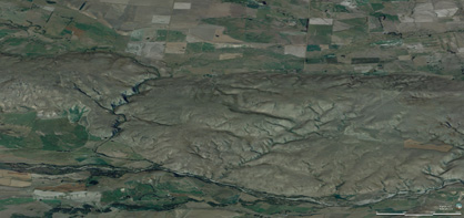 Oblique view of the Raggedy Range from the northwest, with Manuherikia River in foreground and Poolburn valley in background. The smooth gentle slopes of the range reflect the folded structure of the schist bedrock, and this fold is still developing as the range rises. The rising range has forced the Poolburn to cut a deep gorge through the range (left), through which the rail trail passes.