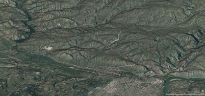 Oblique view of Tucker Hill from the northwest, with Manuherikia River, rail trail, and town of Alexandra in the foreground. The rugged topography results from uplift of schist bedrock along faults that have been active periodically for 100 million years. A white scar at centre left (near the Lower Manorburn Dam) is a remnant of 20 million year old sediments that have been uplifted and tilted along a fault zone.