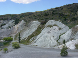 Clay-altered greywacke (white, centre and right) at the Miocene unconformity beneath gold-bearing quartz gravels (left) at Blue Lake, St Bathans The Miocene unconformity and quartz gravels dip ~30° to left.