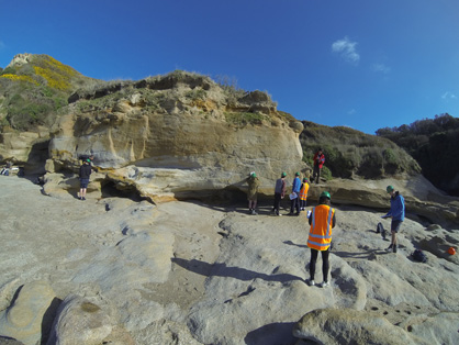 Students logging a section of exposed rock near the Wangaloa Domain along the south Otago coastline.