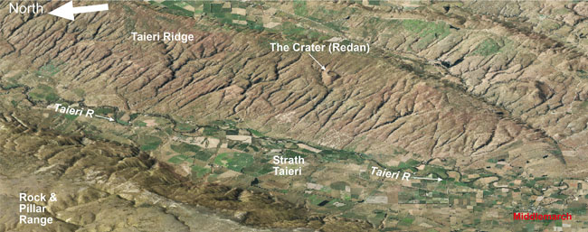 Oblique view of the Strath Taieri basin and Middlemarch township, between two actively rising schist ridges: Rock & Pillar Range and Taieri Ridge. The Otago Central Rail Trail runs parallel to the Taieri River on the western side of the valley, northwards from Middlemarch. The Crater (also called Redan) on Taieri Ridge was formed by an explosive volcanic eruption 25 million years ago, when the land was near to sea level. The crater rim is defined by fragmental schist and volcanic material blown out of the eruption cavity.