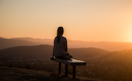 Person sitting alone near dusk on a hilltop thumb