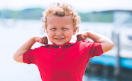 Child in red t-shirt flexing muscles