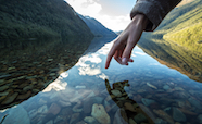 Hand reaching into a scenic river thumbnail