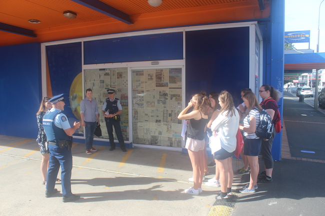Students look on as Police arrest two law staff during a role play