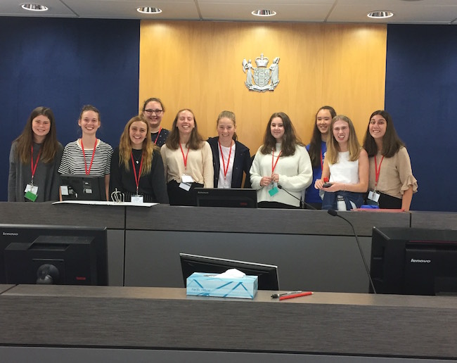 Ten students stand behind the Judge's bench
