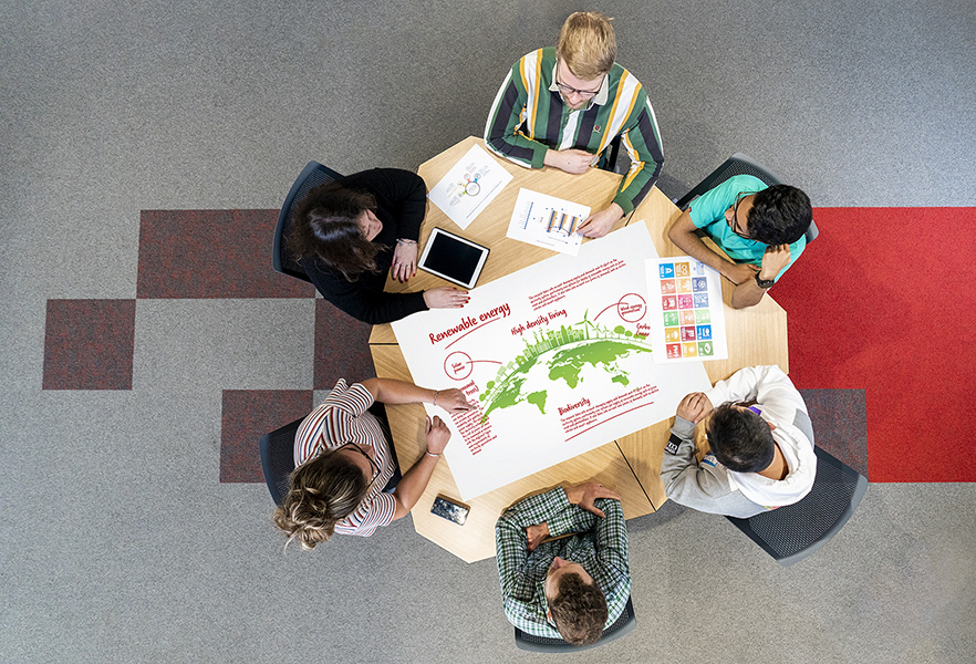 Arial view of  6 students at a table looking at sustainablility artwork image 1x