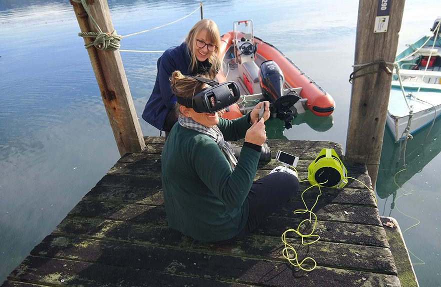 2 females sitting on the wharf with technical  marine equipment 1x