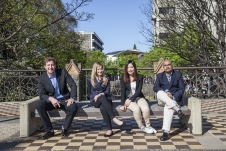 Four MBA students sitting on a park bench