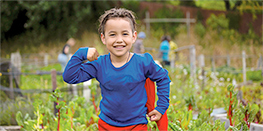 Child in cape at community garden