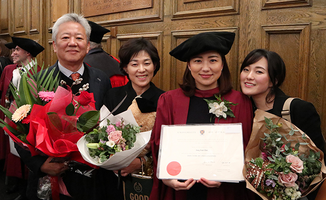 Joanne Choi PhD graduation day, with her parents and younger sister image