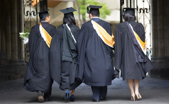 Four Graduating students walking through an archway.