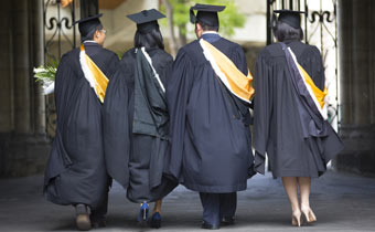 4 students in graduation gowns walking away from the camera