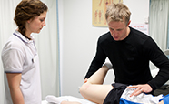 A Dunedin physiotherapist treats a patient's leg, observed by a physiotherapy student thumbnail