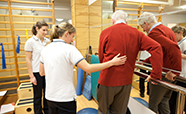 Two student physiotherapists help an elderly many to walk thumbnail