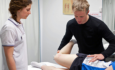 Two physiotherapists treating a patient