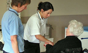 Two physiotherapists greeting an elderly patient in a wheelchair