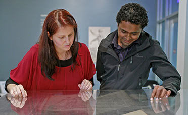 Two graduate students look at historic documents