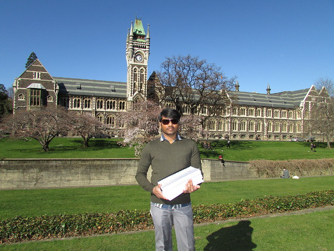 Ashokan Arumugam standing outside the University of Otago Clocktower