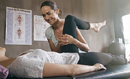 Physiotherapist doing leg work with a patient