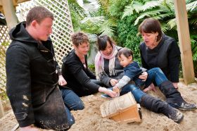 Drs Damian Scarf, Julien Gross and Prof Harlene Hayne in sandpit with mother and child research participants