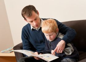 Father reading to son in Assoc Prof Elaine Reese's Research Lab