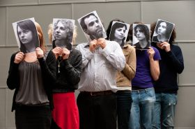 Prof Jamin Halberstadt with students holding monochrome photos in front of their faces
